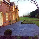 A slate patio compliments house materials and the fresh green of Buxus sempervirens (box) and fresh perennial growth.