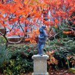 A lead statue with a firery backdrop of stagshorn sumac (Rhus hirta).