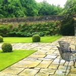 A simple elegant formula of york terracing, sharp edged lawn, box balls and well trained wall plants.