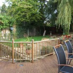 A low quality timber decking and formula ballustrate visibly fences off the stream and rest of the garden.