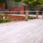 Existing red stained decking replaced with reclaimed oak boards, with bespoke post and rail surround.   Hazel hurdles and large faux lead containers planted with neat evergreen Osmanthus. Other planting by client.